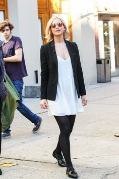 Jennifer Lawrence wears a white dress with black tights, black loafers and a black blazer.