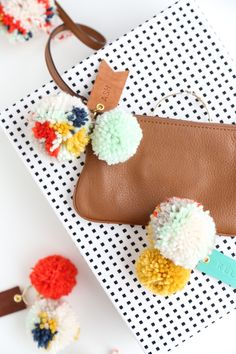 Dress up your carryall with DIY pom pom and leather luggage tags.