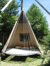 Trampoline recycled as a tipi style suspended swinging bed.