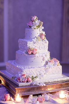 "Wonderful four-tier white wedding cake with pink flowers and white ""pearls."""