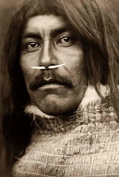 You are looking at an educational picture of Qa Hila. It was taken in 1914 by Edward S. Curtis.    The picture presents Qa hila, a Koprino man, bust portrait, facing front, with bone in nose.    We have created this collection of pictures primarily to serve as an easy to access educational tool. Contact curator@old-picture.com.