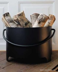 Simple black metal container is a crisp and clean way to store firewood inside.