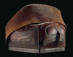 A bentwood food dish with its cover of woven cedar bark.   The main figure is that of a Hawk; at the opposite end is an inverted human figure.     Collected in Skidegate circa 1900 by Charles F. Newcombe.