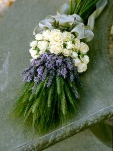 Green wheat forms the basis, symbolizing fertility and prosperity. Lavender adds its lovely fragrance and wishes for luck, devotion, and happiness. Roses, are of course, for love, beauty, and innocence.