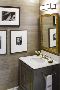 Grasscloth wallpaper makes for a rich backdrop to this glam bathroom featuring marble countertops, grey lacquer cabinetry, and brass fixtures. {Cullman & Kravis}
