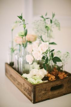 a cluster of flower vases in an old soda crate wedding centerpiece / http://www.deerpearlflowers.com/unique-wedding-centerpiece-ideas/
