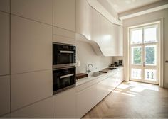 Curved overhead kitchen cabinet in a home by Alma-Nac.
