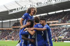 Defender David Luiz climbs atop the backs of his team-mates after Chelsea took the lead against Hull