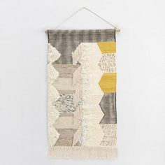 Gray and white graphic patterns with splashes of mustard yellow and hints of shimmering metallic thread come together in our woven masterpiece. Hang it on the wall to instantly infuse your space with a chic midcentury-modern vibe.