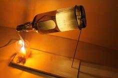 Lampada da tavolo in legno e vetro. In particolare il legno ( abete ) è ottenuto da scarti di lavorazioni precedenti mentre la bottiglia monta una struttura portalampada al suo interno creata appositamente per lasciar trasparire luce in modo diffuso. L'altra lampadina è collocata nel bicchiere in modo tale da dare una continuità al flusso di luce che fuoriesce dalla bottiglia.