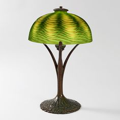 """This is not contemporary - image from a gallery of vintage and/or antique objects. """"Favrile"""" Tiffany Lamp  A Tiffany Studios New York Favrile glass and patinated bronze table lamp, featuring an iridescent green """"Damascene"""" shade atop a patinated bronze """"Ruffle"""" base."""
