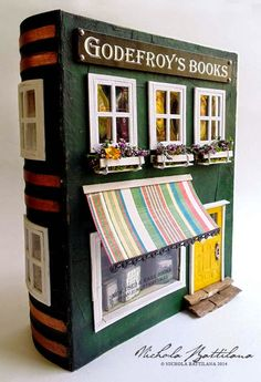 This adorable fairy door, miniature, dollhouse display is a book shop created in a book.  From Pixie Hill.com.