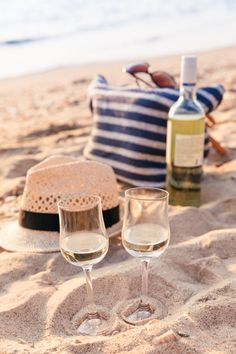 Two glasses of white wine on the beach, next to a man's hat and blue&white striped picnic bag.