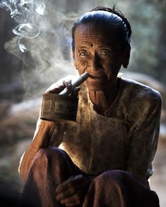 A Grandmother having her evening cheroot (cigar) in a small village in Myanmar, by James Khoo We Are The World, People Around The World, Around The Worlds, Beautiful World, Beautiful People, Old Faces, Interesting Faces, World Cultures, Photos