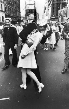 """""""O Beijo"""" foi clicado quando multidões começaram a tomar as ruas de Nova York para celebrar a notícia de que o fim da guerra havia sido declarado. Segundo o fotógrafo Alfred Eisenstaedt, as pessoas vinham de bares, cafés, restaurantes, cinemas etc. e, entre elas estavam Greta Zimmer Friedman e George Mendonsa, dois completos desconhecidos."""