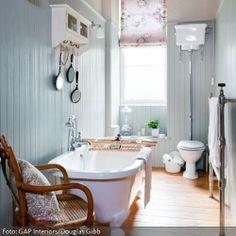 Die Holzverkleidung in Hellblau kombiniert mit dem Blumenmuster-Rollo erzeugt eine warme Atmosphäre, die an ein Bauerhaus erinnert. Dazu passt ein schöner Dielenboden – da Holz als Bodenbelag im Bad wegen der Feuchtigkeit oft schwierig ist, kann man heutzutage auf Fliesen in Holzoptik zurückgreifen. Die freistehende Badewanne mit den zierlichen Löwenfüßen ist das Herzstück des Badezimmer im Landhausstil.
