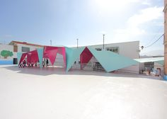 Thin sheets of brightly painted steel have been folded to create this origami-inspired canopy, designed to shelter a school playground.