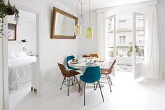 Living comedor en puro blanco, con acentos de color turquesa, mostaza y marrón a través de los accesorios.