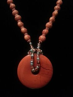 Red jasper pendant, colored beads, and wood beads