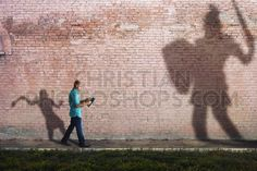 A man reads a Bible while his shadow is David fighting goliath.