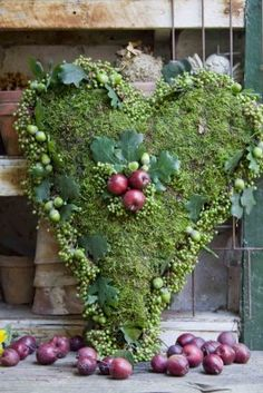 An unusual take on winter decor: moss, oak leaves, and apples in a heart shape.