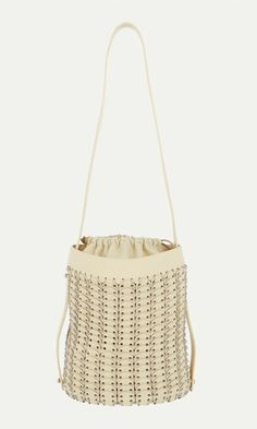 Paco Rabanne ivory calfskin bucket bag is styled with a chain mail cylindrical exterior crafted of ivory calfskin discs and silvertone rings.