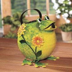 "Roly-poly frog watering can is a fun and functional home accent, indoors or out. Easy carry handle. Handcrafted and handpainted metal with a super-shiny, high-gloss finish. 9"" high. This product has L"