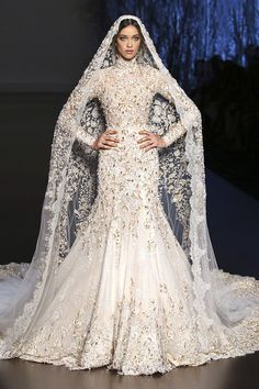 Off white and silver Chantilly lace and layered tulle fishtail bridal gown, printed tulle cape and veil, hand embroidered with gold and silver crystals, pearls and silk hand embroidery.
