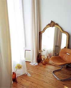 tan leather and chrome chair with ornate vintage gold mirror. / sfgirlbybay