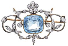 AQUAMARINE AND DIAMOND BROOCH, CIRCA 1910   Centring a cushion shaped aquamarine weighing approximately 4.00 carats within an openwork surround of foliate and scroll design highlighted with circular cut diamonds, mounted in 15ct gold and platinum.