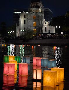 Paper lanterns float in the Motoyasu River in front of the Atomic Bomb Dome (background) at the Peace Memorial Park in Hiroshima on August 6, 2014. The Japanese western city marked the 69th anniversary of the world's first atomic attack. AFP PHOTO.