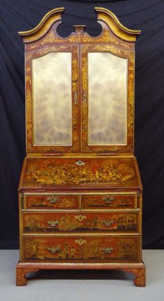 "A George II Parcel-Gilt Scarlet-Japanned Bureau Cabinet, CIRCA 1740, Height: 93"" Width: 39"" Depth: 22 3/4"" - With broken swan's neck pediment above a pair of beveled mirrored doors enclosing a fitted interior above a fall front opening to a conforming fitted interior, with two short and two long graduated drawers below, on bracket feet. Decorated throughout with chinoiserie pagoda landscapes, figures, birds and animals."
