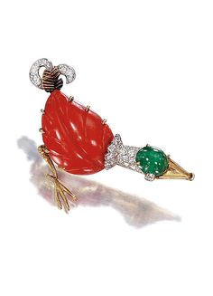 EMERALD PIN, CORAL, DIAMOND AND GOLD BY CARTIER TO 1960   contained a duck head adorned with a round cabochon emerald, the body formed of a sheet of carved coral, neck, tail and eyes accented with diamonds.