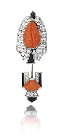 Art Deco coral | Diamond and onyx cliquet pin | circa 1925 |  Each terminal set with a central section of corallium rubrum, the larger with foliate motif carving, within a millegrain-set diamond surround of brilliant, old brilliant and single-cut diamonds, with vari-cut onyx accents | Numbered K324F, cased by Cartier.