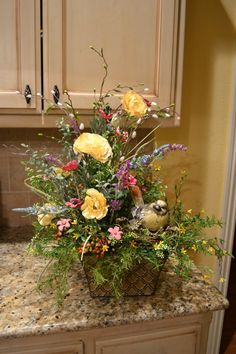 This arrangement is perfect for the upcoming spring and summer months. It is full of colorful flowers and berries and has a cute little bird