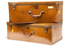 Set of two trunks made from pressed cardboard painted and polished to resemble leather; used for carrying fabric samples.