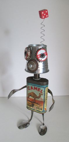 CAMEL LIPS is a very unique found object sculpture made from junk objects that include an antique Camel tube patch kit container, beer bottle caps, jeans button, mini bucket tin, forks, spoons, circuit board, wire, a spring, etc. This is a one of a kind piece of folk art that stands out and makes for a great conversation piece. Perfect for work, office, restaurants, home décor, art galleries, etc. The lid on the Camel tin does come off and would be perfect for hiding and storing items like…