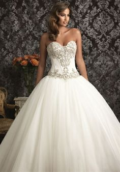 An exquisite ball gown in rich satin and English Net. The strapless bodice features a sweetheart neckline, delicate boning, and Swarovski crystals. The ball gown skirt is gathered and is finished with a chapel length train.