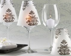 Fashionable white and black damask vellum shades instantly turn ordinary wine glasses into elegant table lamps for your special event.  Guest table decor