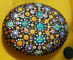 A very meticulously handpainted mandala stone painted in a way that the dots are raised to the touch. Rock measures 3 inches at the long and