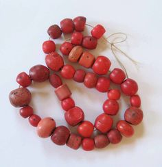 This is a strand of what are called Sherpa Beads or Sherpa coral. Made to simulate coral (in India, China, or Europe) and traded to Nepal in the early