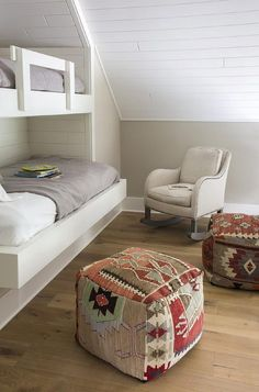 Cottage kids' bedroom features an upholstered rocking chair and kilim poufs placed in front of a wall fitted with recessed bunk beds dressed in white and gray bedding.