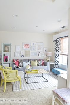 Gray couch with pastel throw pillows, pop of yellow, white and gray striped rug, gallery wall. ❋