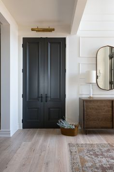 A welcoming front entry with wall panel details, black doors and picture light from a Rural Alberta Country House, Interior Design by Calgary Design Studio Nyla Free Designs Inc, Architecture: Dejong Design Associates, Photography: Phil Crozier, #nylafreedesigns #calgaryinteriordesigners #blackdoors #wallpanelling #countryhouse