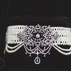 Woven seed pearl choker with elegant graduated pearl drapes and stunning diamond and white gold floral motif brooch.