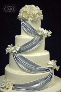 White cake with a lilac courtain and white flowers on top of the cake.
