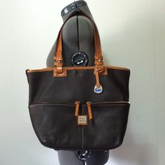 Dooney & Bourke Brown Leather Tote Bag Dooney & Bourke brown leather w/ honey colored handles and edging. Tag was not bought with bag but matches perfect and will come with the bag. Has yellow reg. card and stickers are still inside the pocket. In great condition, hardly any signs of use, very little on corners. Gold hardware. No dust bag! Snap closure. Can be used two different ways. Bag has been registered. See other listing for more pictures of bag. ⭐️Price is Firm⭐️ Dooney & Bourke Bags…
