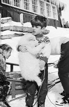 Jan 1966, Sun Valley, Idaho, USA — John F. Kennedy Jr. holds a fuzzy samoyed puppy as his sister Caroline and his mother, Jacqueline Kennedy Onassis, move a dogsled. The family was vacationing here with the family of Senator Robert F. Kennedy. — Image by © Bettmann. (Right) Killy
