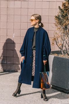 Navy coat, brown top and skirt and orange sunglasses.
