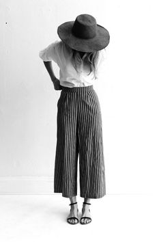 Straw hat, white shirt,striped, wide legged trousers and sandals.